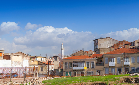 Street view of old Izmir, Turkey. Living houses and mosque under cloudy sky