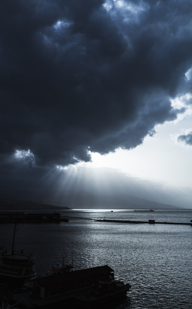 Dark dramatic sky with clouds and sunlight rays over sea. Bay of Izmir. Blue toned photo filter effect Reklamní fotografie