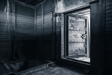 Abstract dark grungy industrial interior with metal walls and open heavy steel door, monochrome photo Фото со стока
