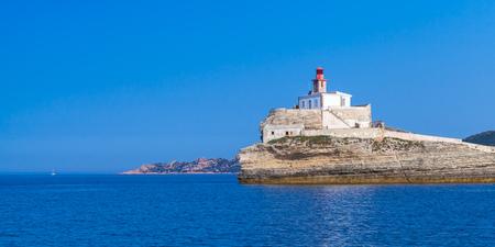 Madonetta, lighthouse tower with red top on coastal rock. Entrance to Bonifacio port. Mountainous Mediterranean island Corsica, Corse-du-Sud, France Stock Photo