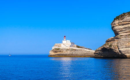Madonetta, lighthouse tower with red top. Entrance to Bonifacio port. Mountainous Mediterranean island Corsica, Corse-du-Sud, France Stock Photo