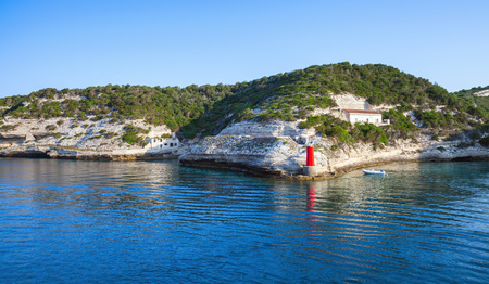 Cliffs with old building and red lighthouse, entrance to the port of Bonifacio, Corsica island, France Stock Photo