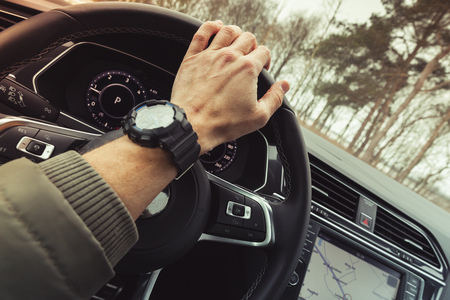 Driver hand holds steering wheel of luxury crossover car. Close-up photo with selective focus and warm tonal correction filter effect
