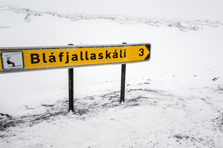 sign post: Yellow Icelandic road sign with direction to sky resort stands on the roadside in cold snowy winter day Stock Photo