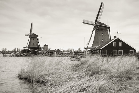 Windmills in Zaanse Schans town. It is one of the popular tourist attractions of the Netherlands. Retro stylized sepia toned monochrome photo