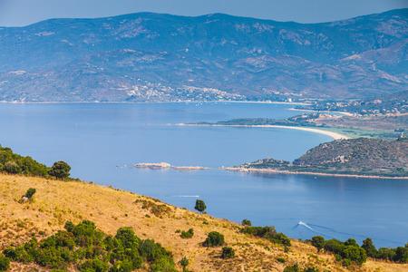 Summer coastal landscape of French mountainous island Corsica. Small trees grow on coastal hills. Piana region, France