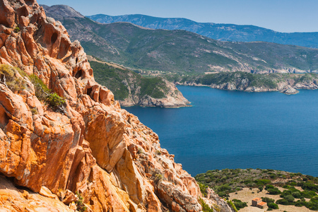 Coastal landscape of Corsica island with red rocks and blue sea water. Viewpoint of Capo Rosso, Piana region Standard-Bild