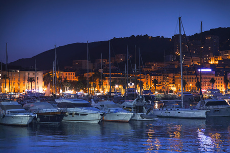 Pleasure yachts and motor boats moored in old port of Ajaccio, Corsica island, France. Dark night photo