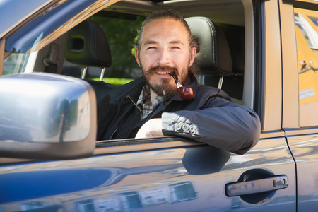 crossover: Smiling Asian man smoking pipe. Driver of modern Japanese crossover suv car, portrait in open car window