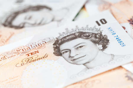Ten pound notes of the Bank of England lay on a table. Close-up photo with selective focus