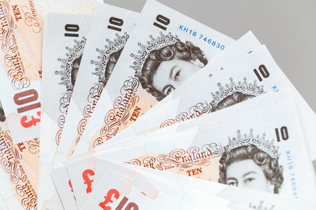 Ten pound notes of the Bank of England. Close-up photo over gray background with selective focus
