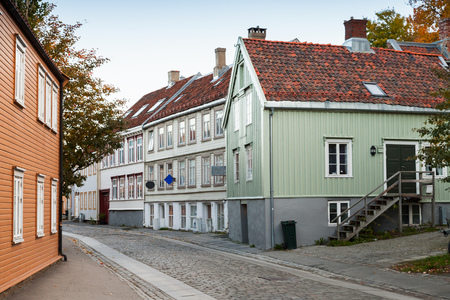 Traditional Scandinavian wooden houses stand along old street in Trondheim, Norway