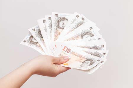 libra esterlina: Diez notas de la libra del Banco de Inglaterra en mano femenina. Close-up foto sobre fondo gris de la pared con el enfoque selectivo