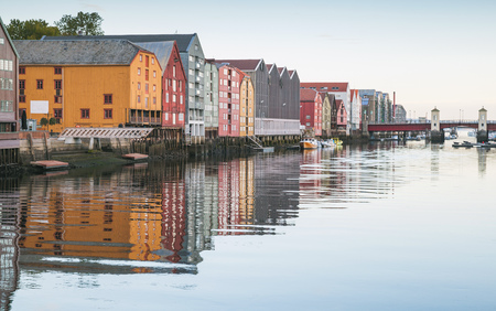 Wooden living houses stand in a row along the river coast. Trondheim, Norway