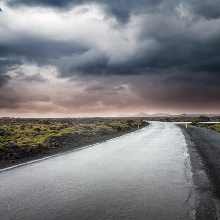 Empty rural road under dark dramatic stormy sky, Reykjavik district, Iceland