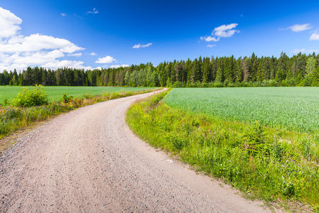 Turning empty rural road under blue sky with clouds in bright summer day. Empty landscape background photo of Finland
