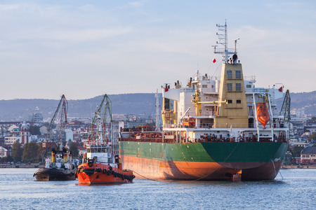 Bulk carrier and tug boats, industrial ship enters in port of Varna, Bulgaria Stock Photo