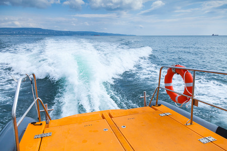 Red lifebuoy hanging on stern railings of fast safety rescue boat