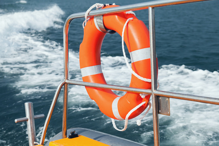 Red lifebuoy hanging on stern railings of fast motor boat