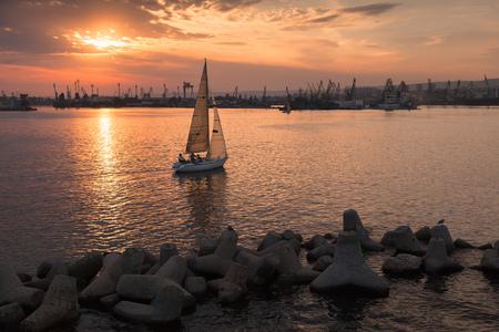 Sailing yacht enters the harbor at sunset. Black Sea, Varna port, Bulgaria