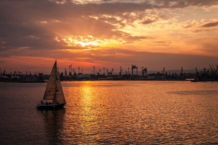 Sailing yacht enters the harbor at the sunset. Black Sea, Varna port, Bulgaria
