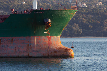 Green bow with red waterline of big industrial cargo ship