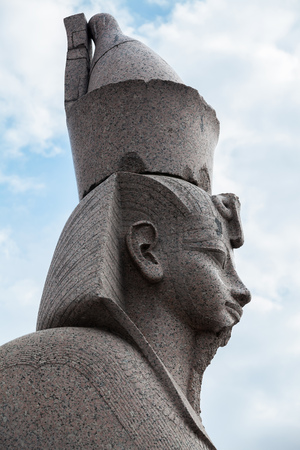 Granite sphinx profile. Ancient monument on blue cloudy sky background. Landmark of Neva river coast in St.Petersburg, Russia Stock Photo