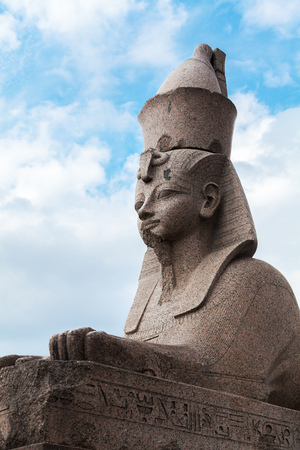 Granite sphinx. Ancient monument on blue cloudy sky background. Landmark of Neva river coast in St.Petersburg, Russia