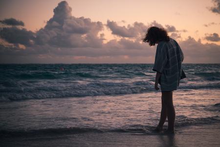 早朝に海の海岸を歩いている女の子のシルエット写真。大西洋上の日の出、ドミニカ共和国、ババロビーチ