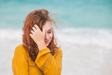 ドミニカ共和国の海の海岸に赤い髪を持つ美しいコーカサスの十代の少女の屋外の肖像画