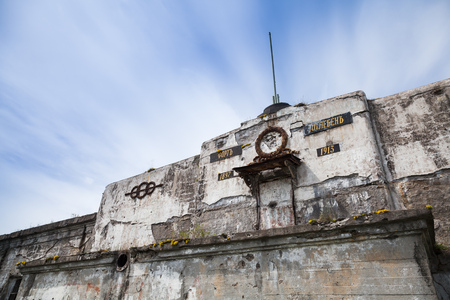 St.Petersburg, Russia - July 5, 2014: Facade of old abandoned fortification from WWII period on island in Gulf of Finland near Saint-Petersburg in Russia. Russian text on the wall mean Fort Totleben Editorial