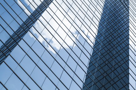 Abstract fragment of modern business architecture, walls made of glass and steel with reflections of cloudy sky