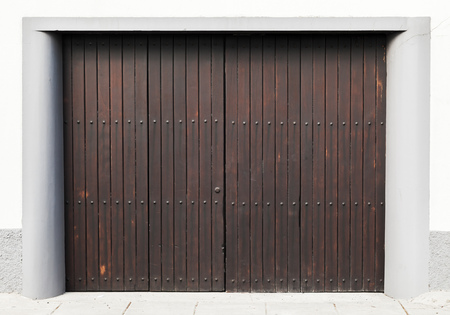 Brown wooden gate in white concrete wall. Background photo texture Stock Photo