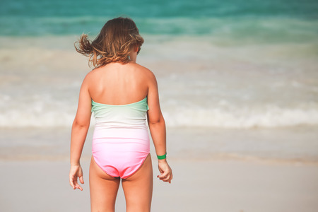 Caucasian blond baby girl in green and pink swimsuit stands on the sea coast, rear view