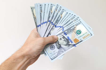Fan of One Hundred Dollars notes in male hand over white wall background Stock Photo