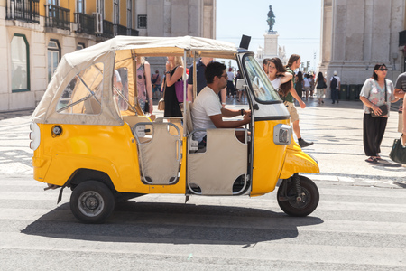 Lisbon, Portugal - August 12, 2017: Yellow Tuk Tuk taxi cab with driver rides the street of Lisbon