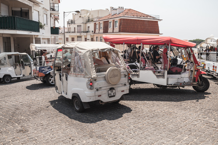 Lisbon, Portugal - August 13, 2017: Tuk Tuk taxi cabs of Lisbon stand on a city square with tourists as a passengers. Piaggio Ape three-wheeled light commercial vehicles produced since 1948 by Piaggio