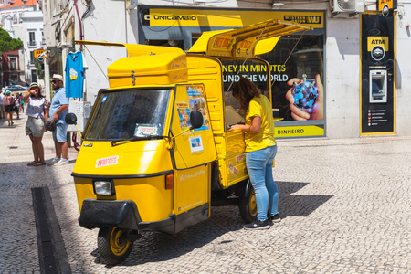 Lisbon, Portugal - August 12, 2017: Yellow Piaggio Ape three-wheeled light commercial vehicle as a touristic attractions ticket office