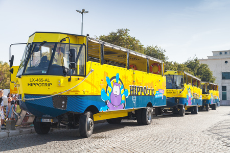 water bus: Lisbon, Portugal - August 15, 2017: Yellow blue amphibian buses operated by Hippotrip stand on a bus stop, popular touristic transportation attraction Editorial
