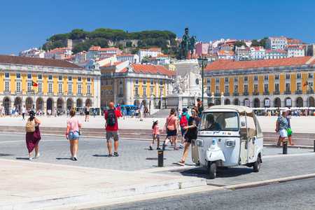 Lisbon, Portugal - August 12, 2017: White Tuk Tuk taxi cab stands on Commerce Square in Lisbon. Ordinary people and tourists walk nearby Editorial