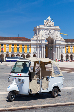 Lisbon, Portugal - August 12, 2017: White Tuk Tuk taxi cab with driver stands on Commerce Square in Lisbon. Piaggio Ape three-wheeled light commercial vehicle produced since 1948 by Piaggio Editorial