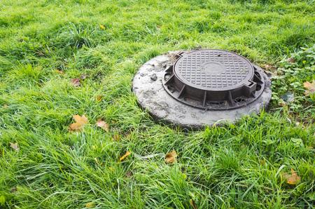 Tapa de alcantarilla redonda en hierba verde Foto de archivo - 87967165