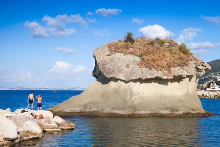 Lacco Ameno, Italy - August 17, 2015: Ordinary people rests near Il Fungo. Famous rock with mushroom shape. Lacco Ameno resort town, Ischia island, Italy