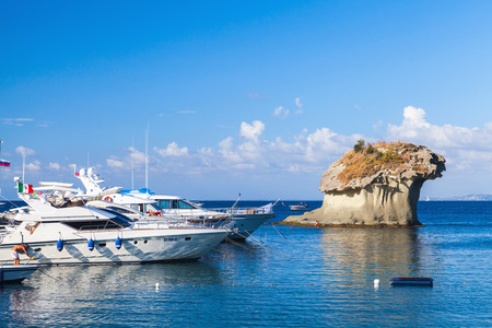 Lacco Ameno, Italy - August 17, 2015: Yachts with passengers on board moored near Il Fungo. Natural landmark, mushroom shaped rock in harbor of Lacco Ameno, Ischia island, Italy Editorial