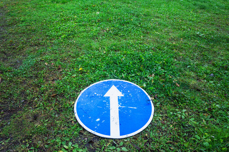 Ahead only, round blue road sign with white arrow lays on green grass Stock Photo
