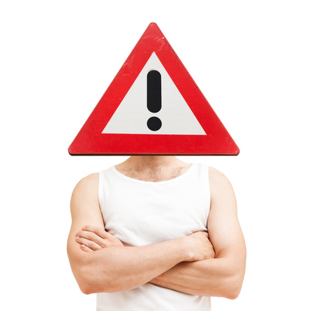 Caution male problem concept. Young sporty Caucasian man with warning signs over face in white shirt with crossing hands isolated on white Stock Photo