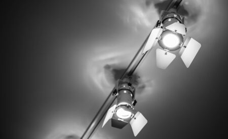 Two spot lights in metal body over ceiling background, stage illumination equipment