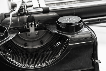 Old manual typewriter machine fragment, black and white photo with soft selective focus