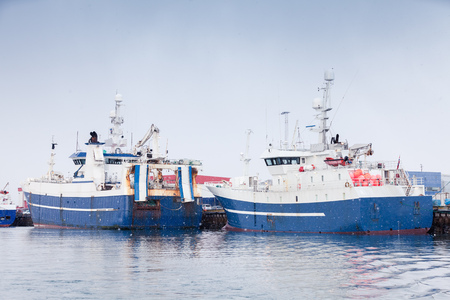 Industrial fishing ships. Blue white trawlers stands moored in port of Reykjavik, Iceland