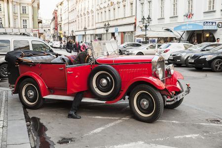 Prague, Czech Republic - April 30, 2017: Driver gets into red vintage oldtimer car on the street of old Prague